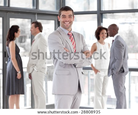 Potrait of a Smiling Businessman standing in Front of Business team - stock photo