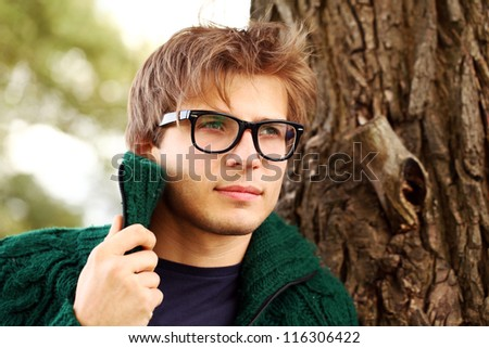 Potrait of handsome and smart guy at cold autumn day in the park - stock photo