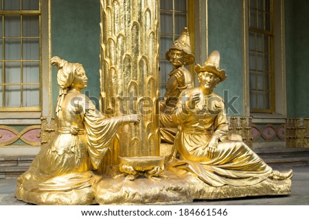 POTSDAM, GERMANY - JULY 15, 2013: Golden statues in front the Chinese house, part of Sanssouci park (18th century). Sanssouci is the former summer palace of Frederick the Great, King of Prussia. - stock photo
