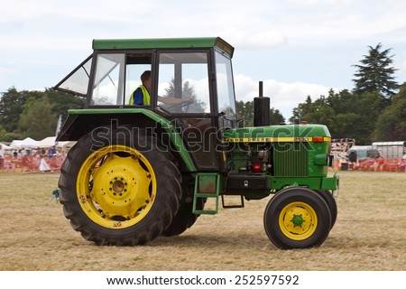 POTTEN END, UK - JULY 27: A vintage John Deere tractor is paraded around the main arena as part of the agricultural machinery show at the Dacorum Steam & Country fair on July 27, 2014 in Potten End - stock photo