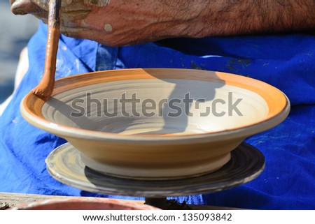 Potter's Hands Adding Finishing Details To Handmade Pottery - stock photo