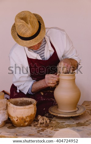 Potter with apron and hat modeling a clay vase by hand using a kick wheel - stock photo