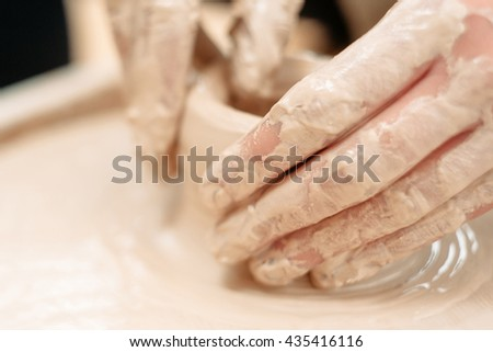 Potters dirty hands on potter wheel close-up. Front view on dirty hands of potter working on potters wheel. Making pottery close-up - stock photo