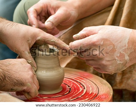 Potters hands and pot on a potter's wheel