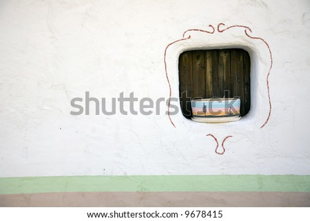 pottery in the window of a quaint southwestern building - stock photo