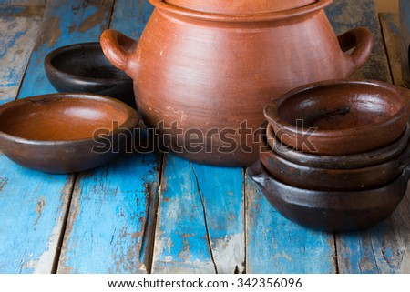 pottery kitchenware on the old blue wooden background - clay dishes and pot