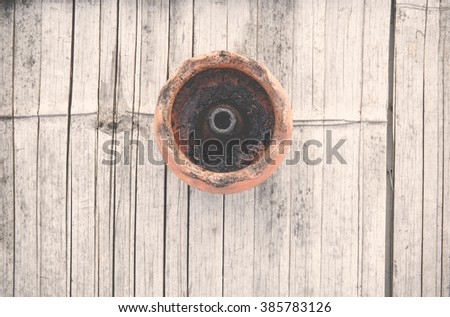 Pottery oil lamp on bamboo background, Top view of local oil lamp in Asia,Thailand.