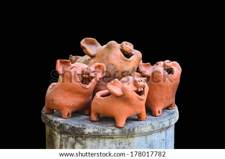 Pottery pig laughing on black background - stock photo