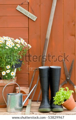 Potting shed with wellington boots, tools, watering can and garden pots - stock photo