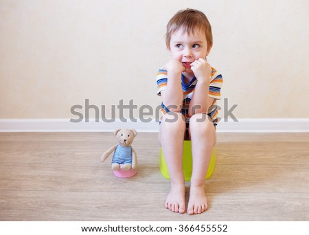 potty training toddler and teddy. child sitting on the pot in the company of his beloved teddy bear toy - stock photo