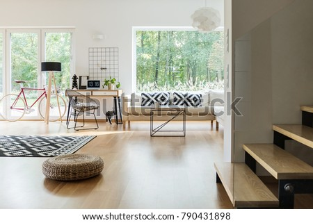 Pouf And Patterned Carpet In Spacious Living Room With Workspace, Red Bike  And Lamp