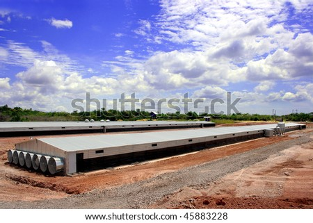 Poultry farm showing houses with a blue sky - stock photo