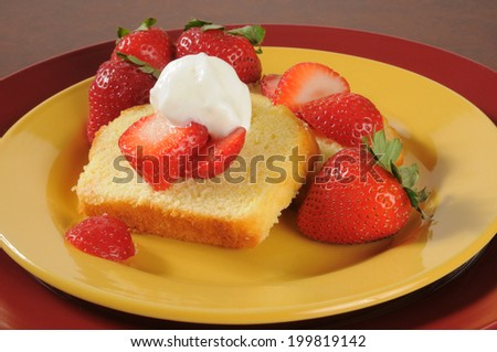 Pound cake slices topped with fresh strawberries and whipped cream, a summertime treat. - stock photo