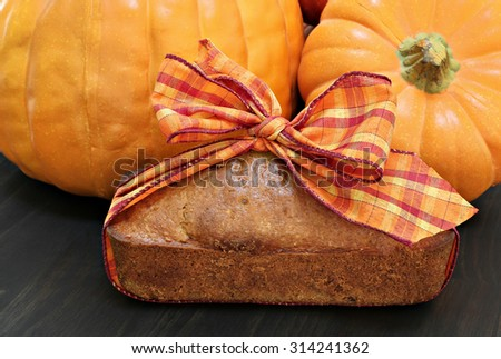 Pound cake wrapped in a festive fall ribbon with pumpkins in the background.  Hostess gift idea. - stock photo