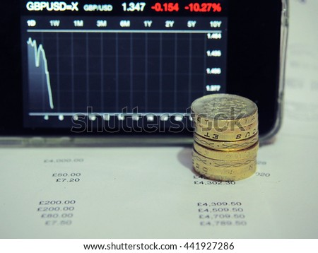 Pound coins with the decreasing graph of UK currency; British Pound (GBP) after EU referendum result brexit win. UK leave EU. Pound sterling crash. - stock photo