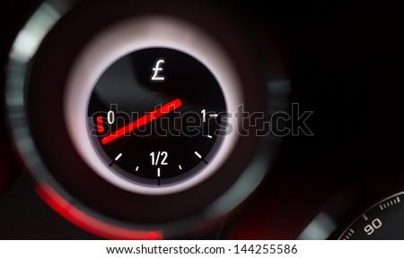 Pound sign fuel gauge nearing empty. - stock photo