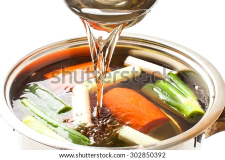 pour broth transparent to the broth pot on white background - stock photo