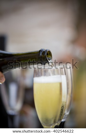 Pour champagne into a glass - stock photo
