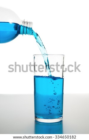 Pour cold water into glass isolated on white background