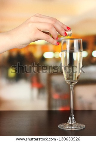 Pour something into glass with drink on wooden table on room background