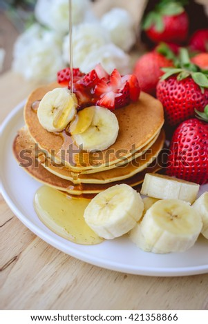 pour syrup on stack of pancake with strawberry and slice of banana on white plate with wooden background - stock photo