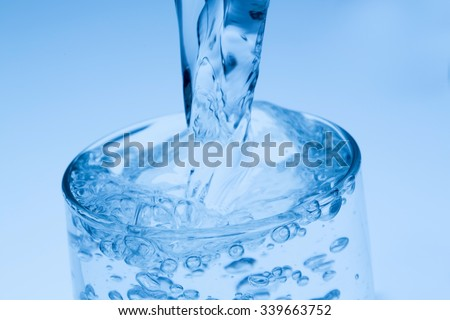 pour water into a glass, symbol photo for drinking water, abundance and waste - stock photo