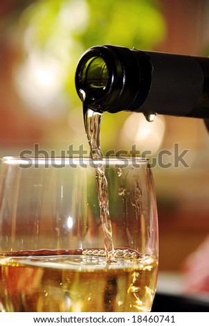 pour wine from green bottle into glass - stock photo