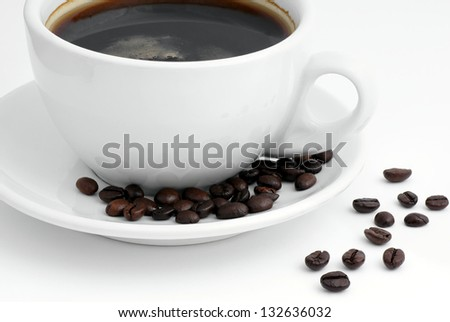 Poured a cup of coffee and roasted beans. - stock photo