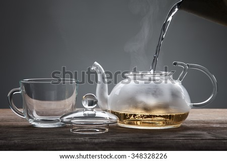 poured from a teapot cup of tea on a wooden table - stock photo