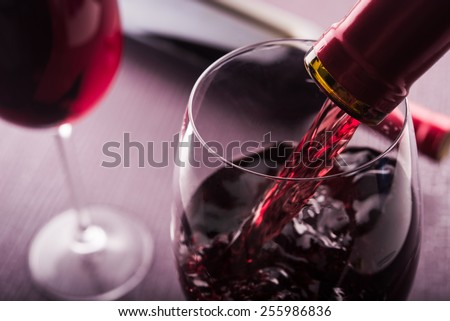 Poured red wine into glass - stock photo