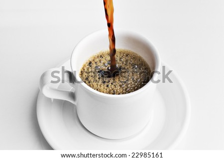 Pouring a cup of coffee on a white tabletop - stock photo