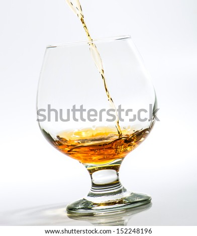 Pouring a glass of brandy on a light background - stock photo