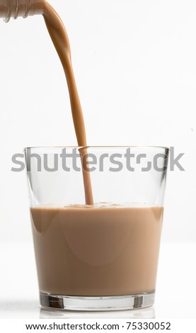 Pouring a glass of chocolate milk - shot in studio on white background - stock photo
