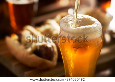 pouring amber beer into mug with bratwursts in background