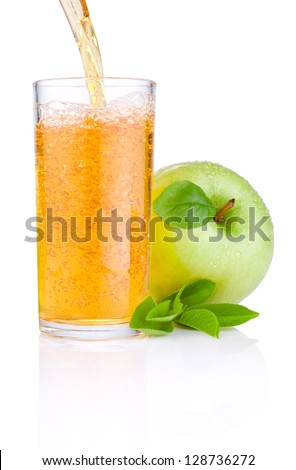 Pouring apple juice into a glass, green juicy apples with green leaf on white background