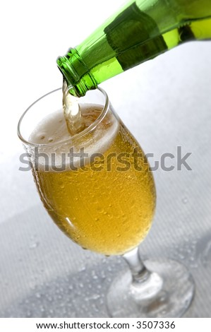 pouring beer from bottle in to glass close up - stock photo