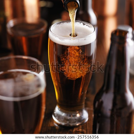 pouring beer from bottle into glass at bar - stock photo