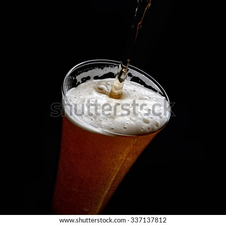 pouring beer in a glass on a black background - stock photo