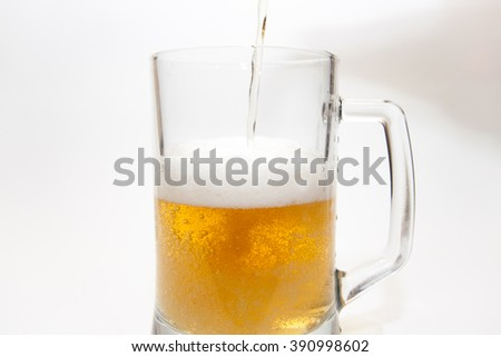 Pouring beer in a mug on a white background