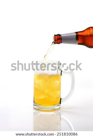 pouring beer in glass on white background - stock photo