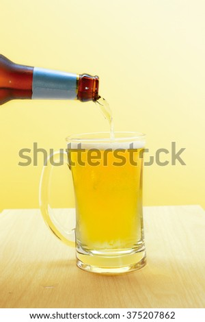 Pouring Beer into glass on wood table - stock photo
