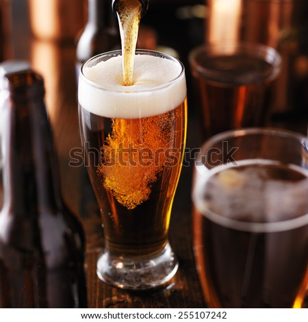 pouring beer into glass on wooden table - stock photo