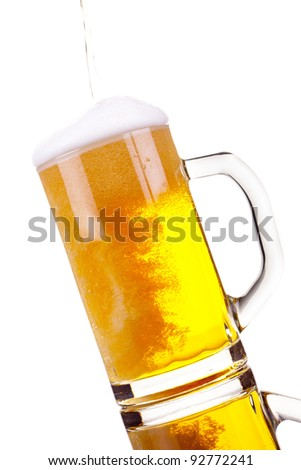 Pouring beer into mug isolated over a white background - stock photo