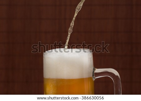 Pouring beer into the mug   - stock photo