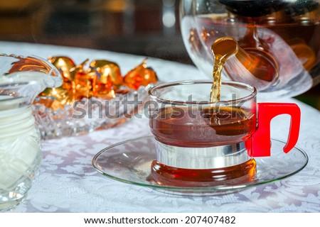 Pouring black tea - stock photo