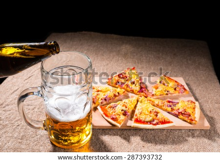 Pouring Bottled Beer into Glass Mug with Meal of Fresh Baked Pizza Arranged in Slices on Wooden Cutting Board on Burlap Covered Table - stock photo