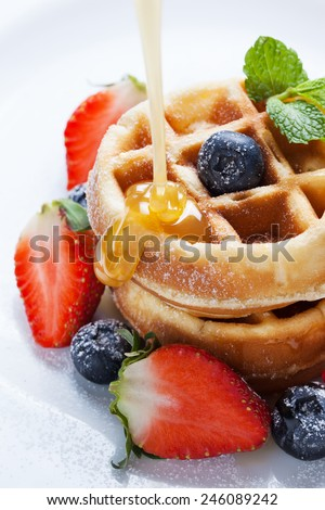 pouring caramel sauce on waffles with strawberry and blueberry - stock photo