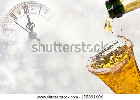 Pouring champagne against holiday lights and clock close to midnight  - stock photo