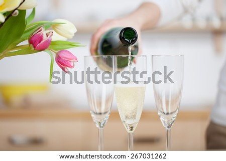Pouring champagne in flutes standing on table - stock photo