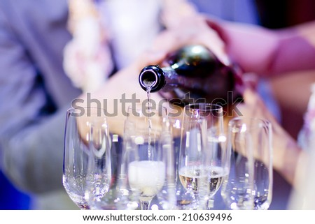 Pouring champagne into fancy glasses - stock photo